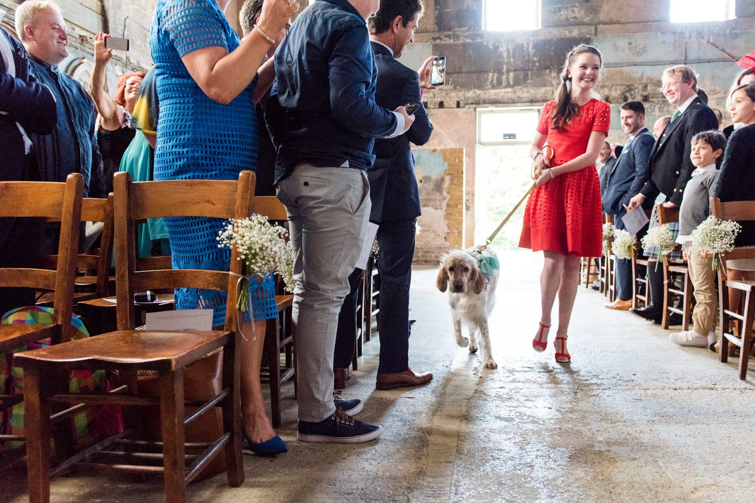 Lady in red with dog walk the aisle for same sex London wedding