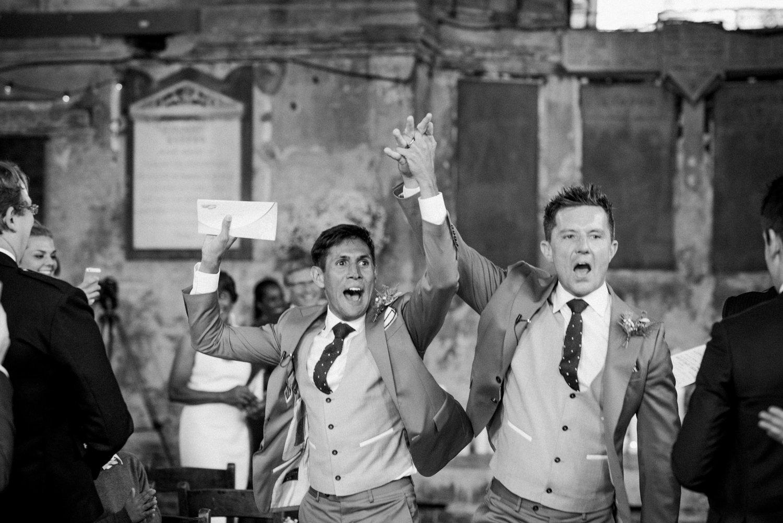 Grooms cheer at same sex wedding Hackey warehouse London