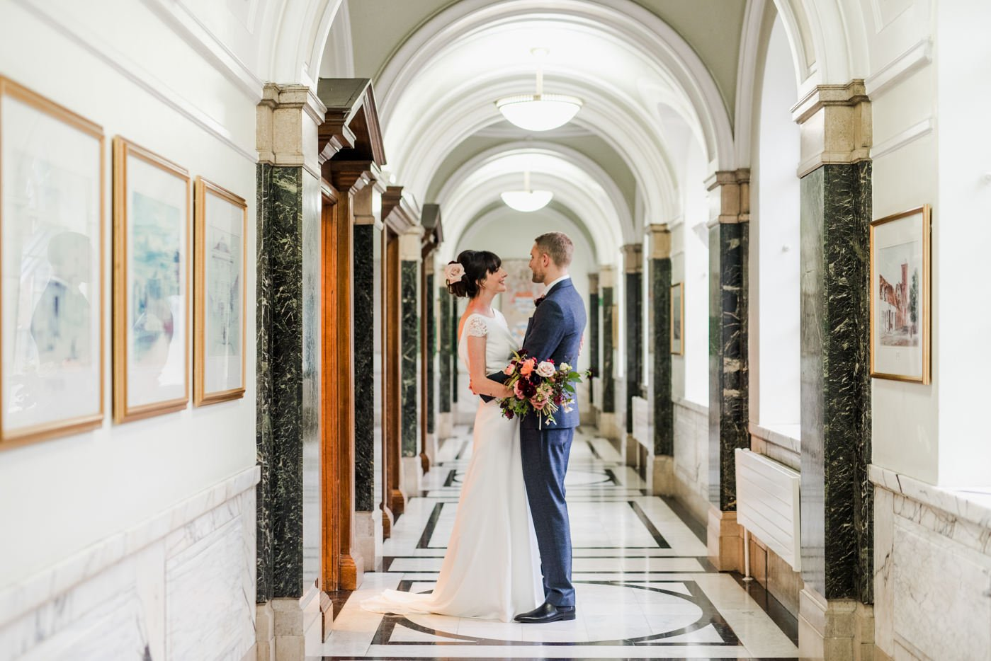 A couple stand in the marble corridor at their wedding ceremony at Islington Town Hall in London
