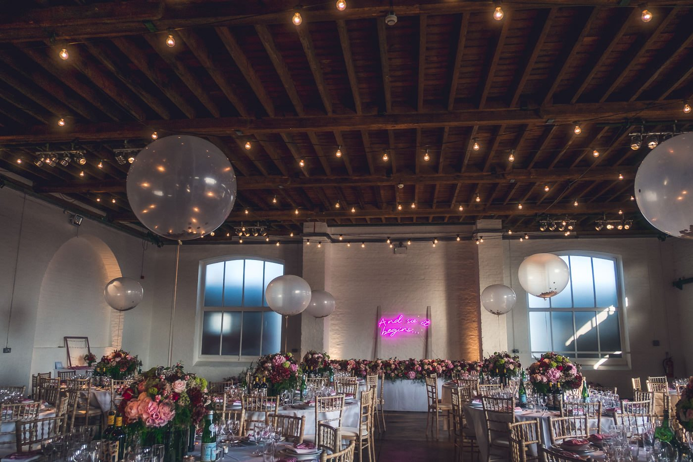 Trinity Buoy Wharf wedding venue set up for dinner with round tables and giant balloons decorating the warehouse