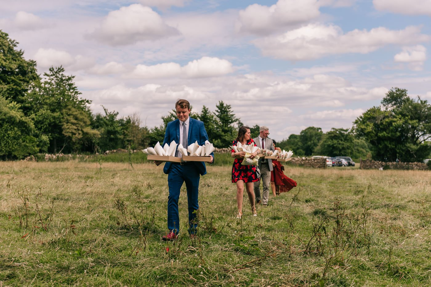guests carrying confetti across a field humanist outdoor wedding