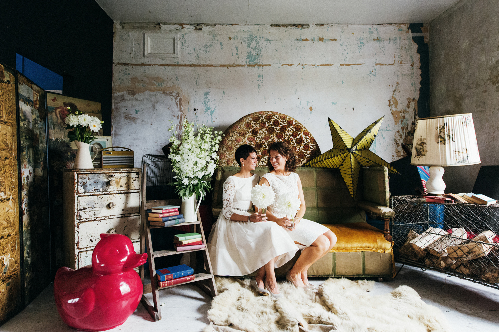 Brides in short dresses sitting on vintage furniture - gay wedding The Roost Dalston wedding - quirky London wedding photographer © Babb Photo