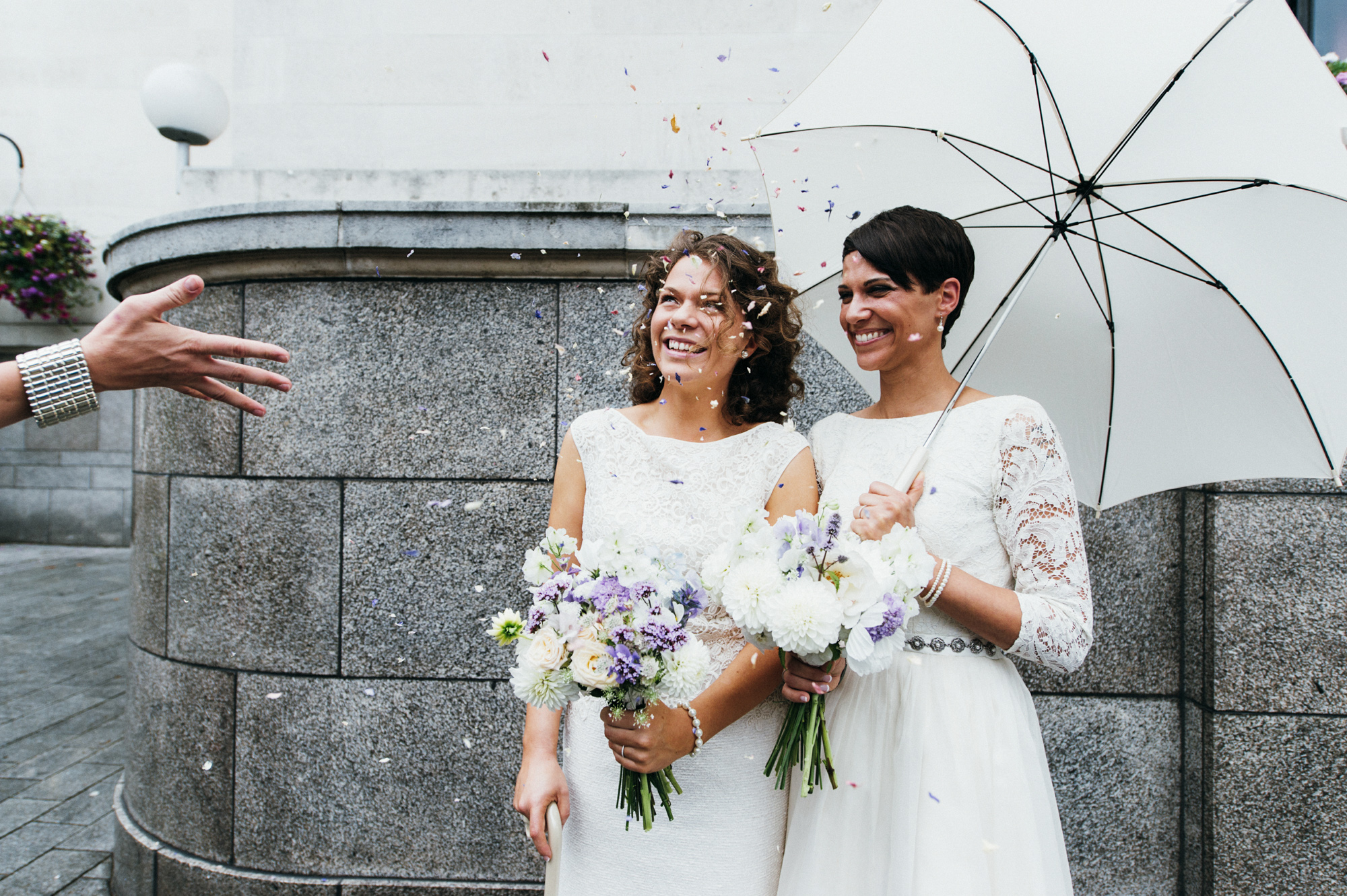 Smiling brides in short lace dresses, bouquets by The Flower Appreciation Society - gay wedding The Roost Dalston wedding - quirky London wedding photographer © Babb Photo
