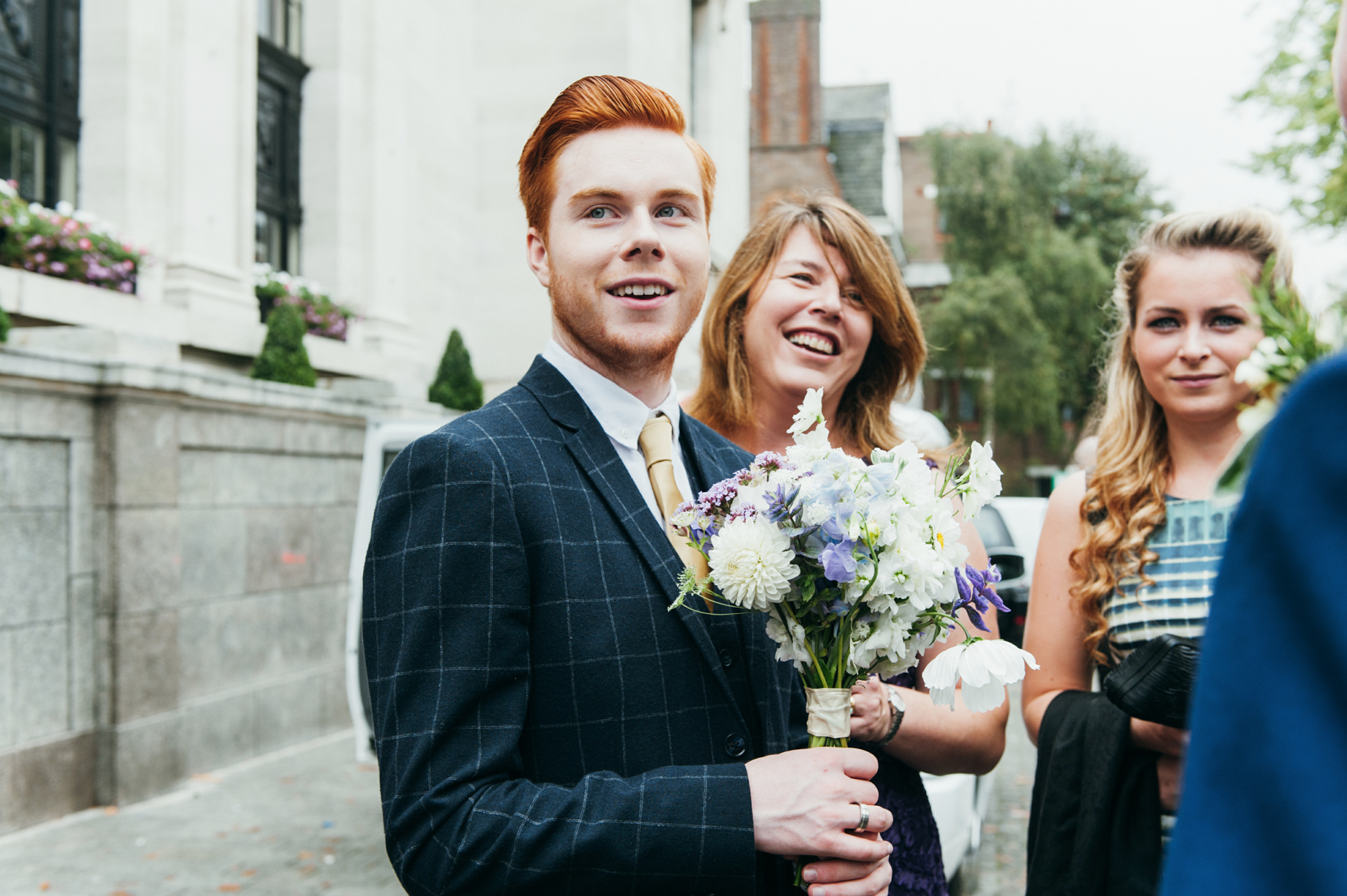 Smiling wedding guest holding bouquet - gay wedding The Roost Dalston wedding - quirky London wedding photographer © Babb Photo