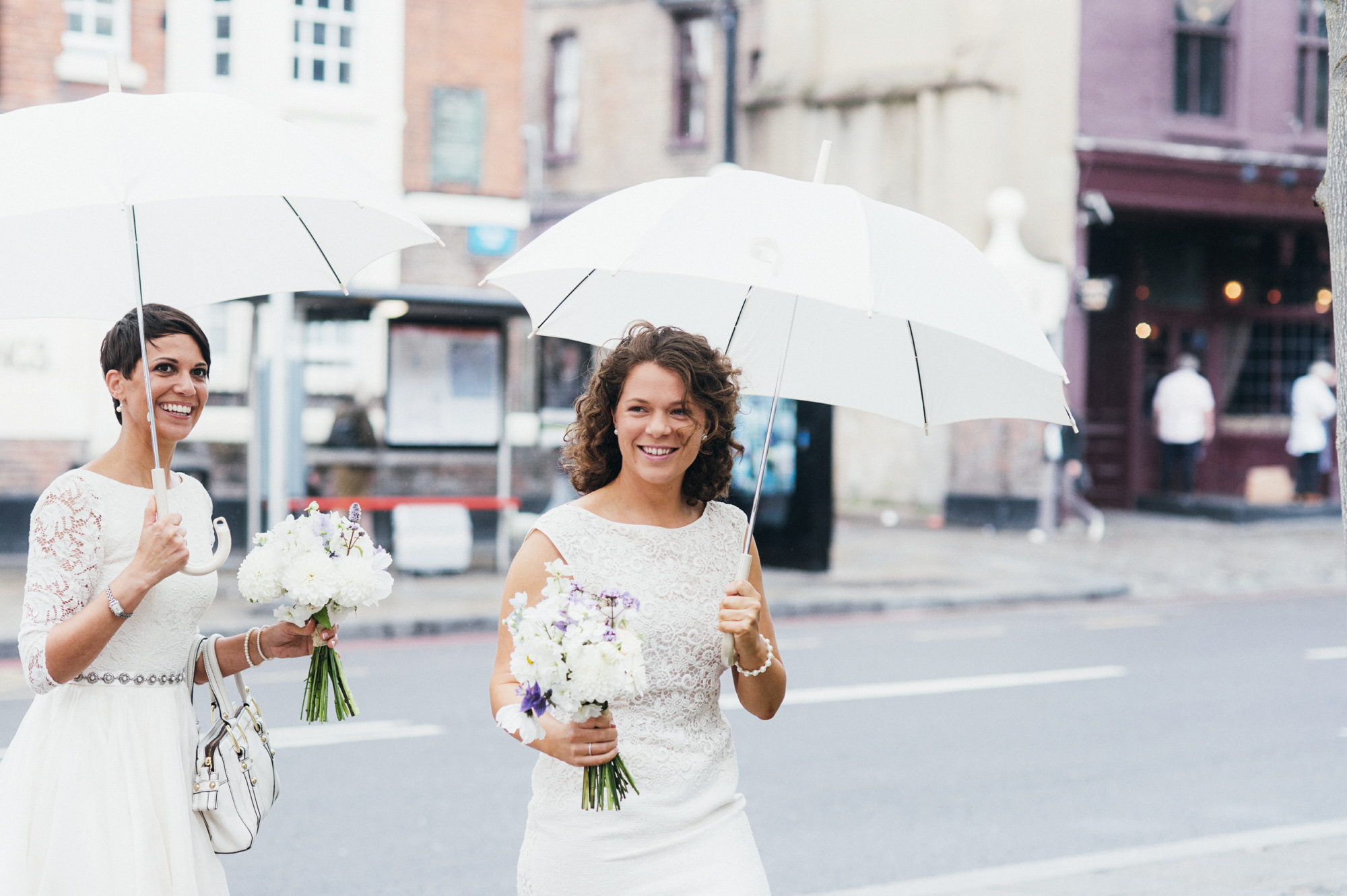 gay wedding brides in lace wedding dresses with white umbrellas - gay wedding The Roost Dalston wedding - quirky London wedding photographer © Babb Photo