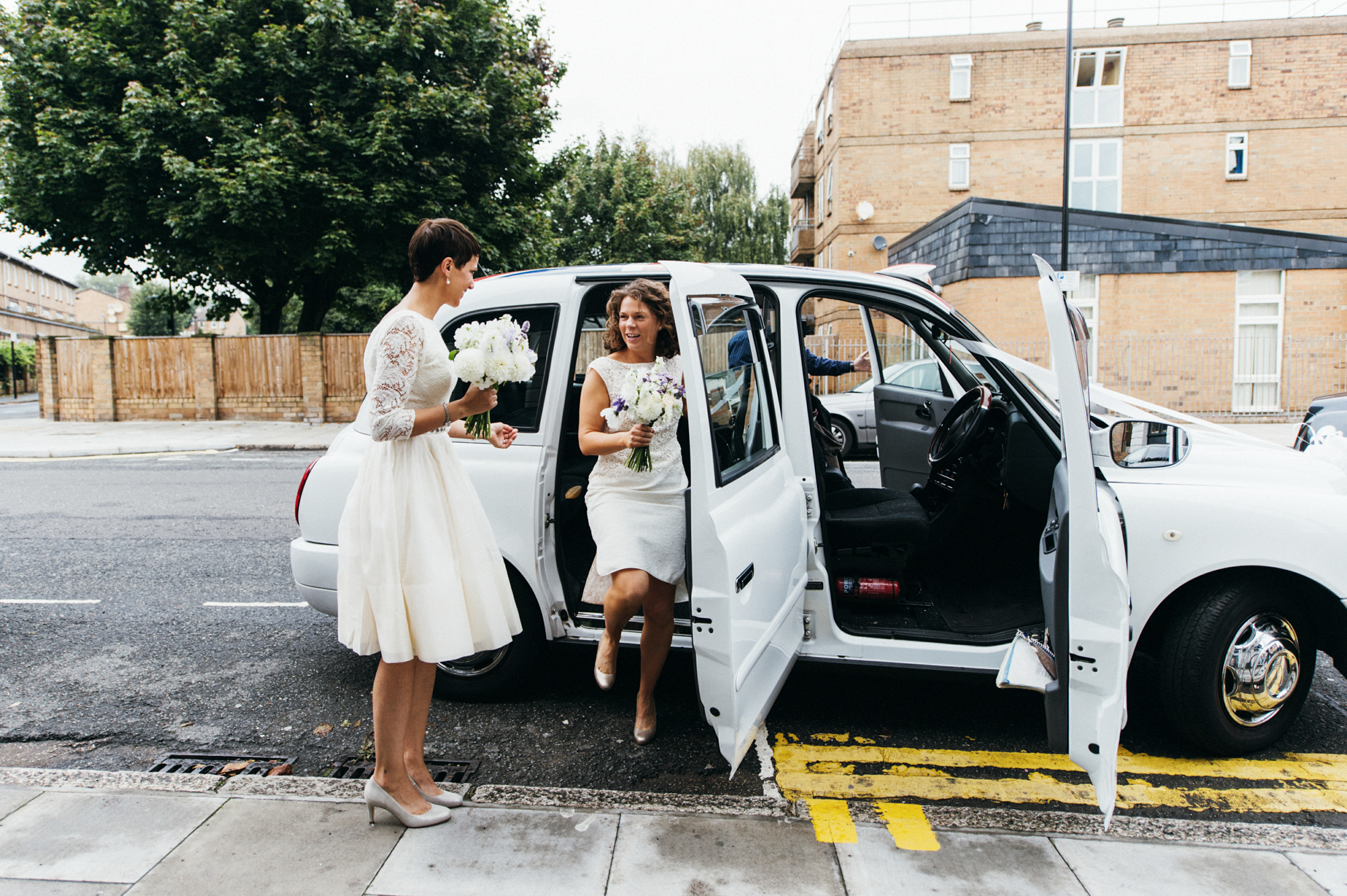 Brides in short lace wedding dresses get out of white Union Jack London taxi - gay wedding The Roost Dalston wedding - quirky London wedding photographer © Babb Photo