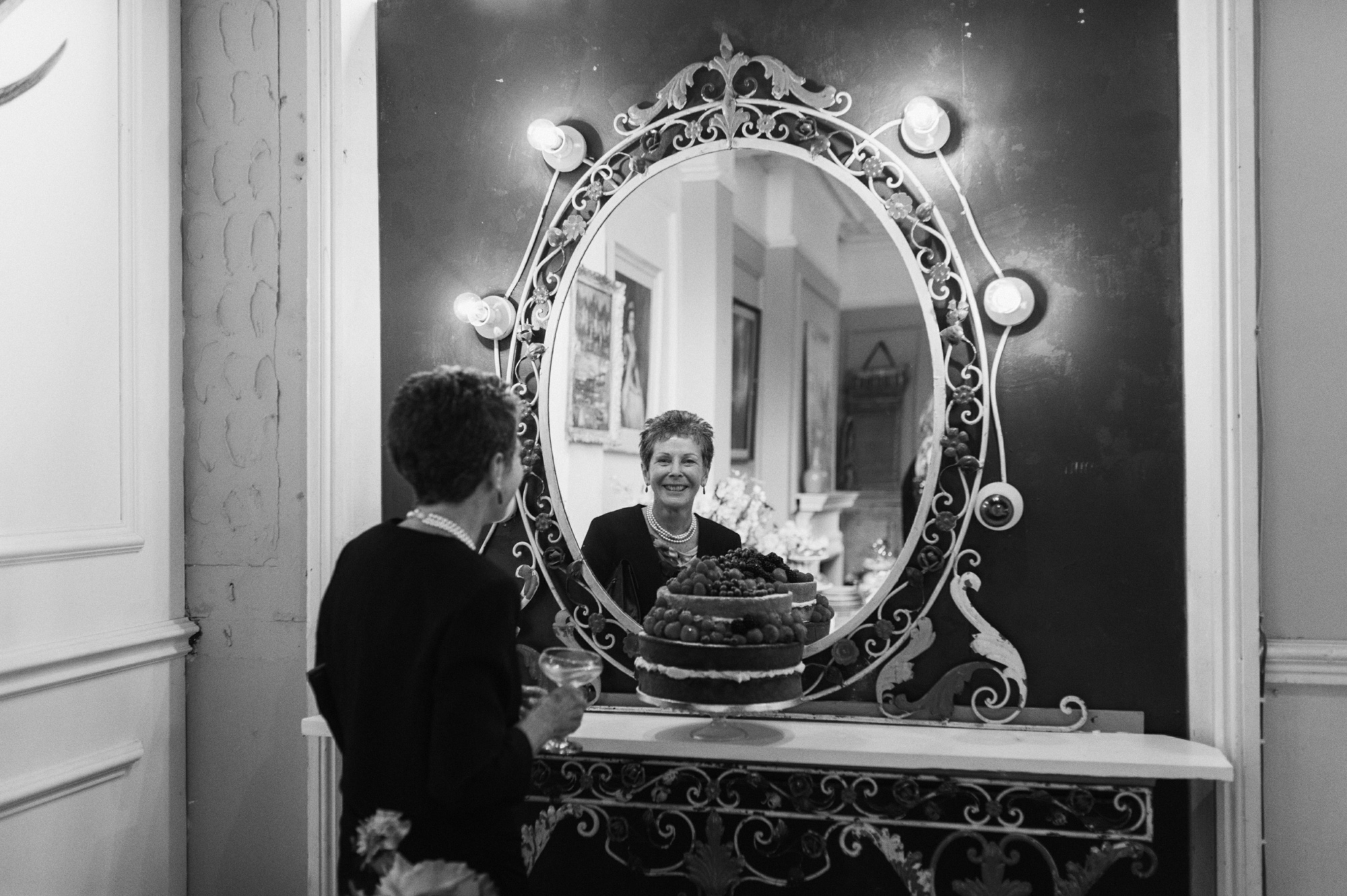 Black and white lady looking in the mirror - gay wedding The Roost Dalston wedding - quirky London wedding photographer © Babb Photo