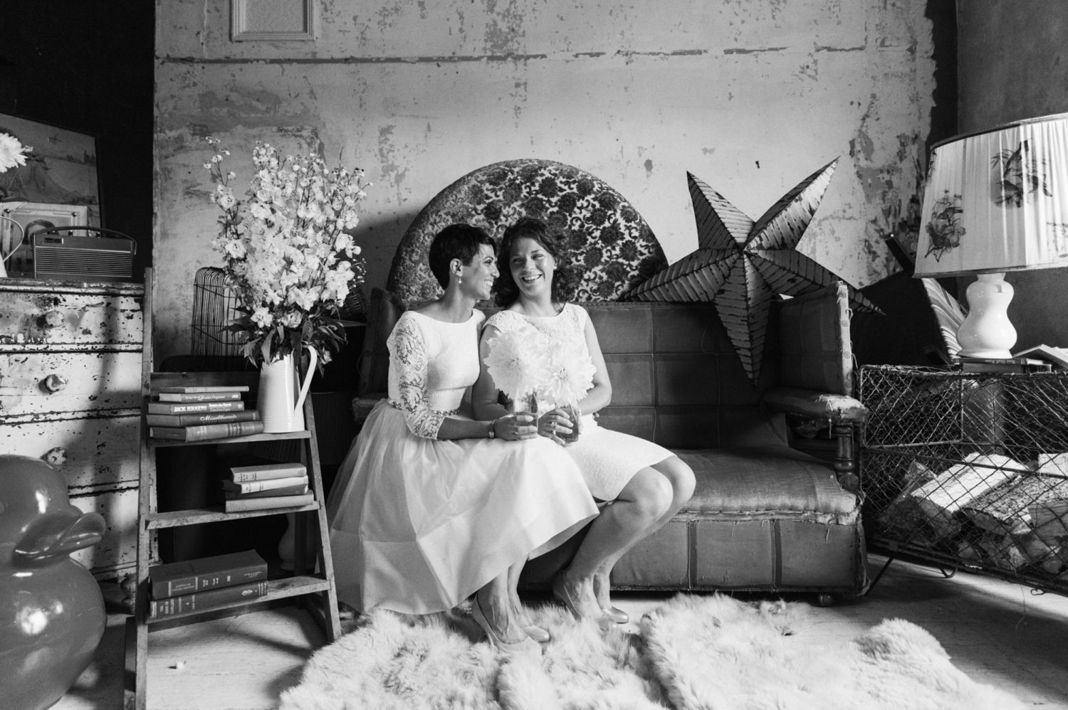 Cute couple sitting on vintage sofa at same sex wedding the roost wedding photography