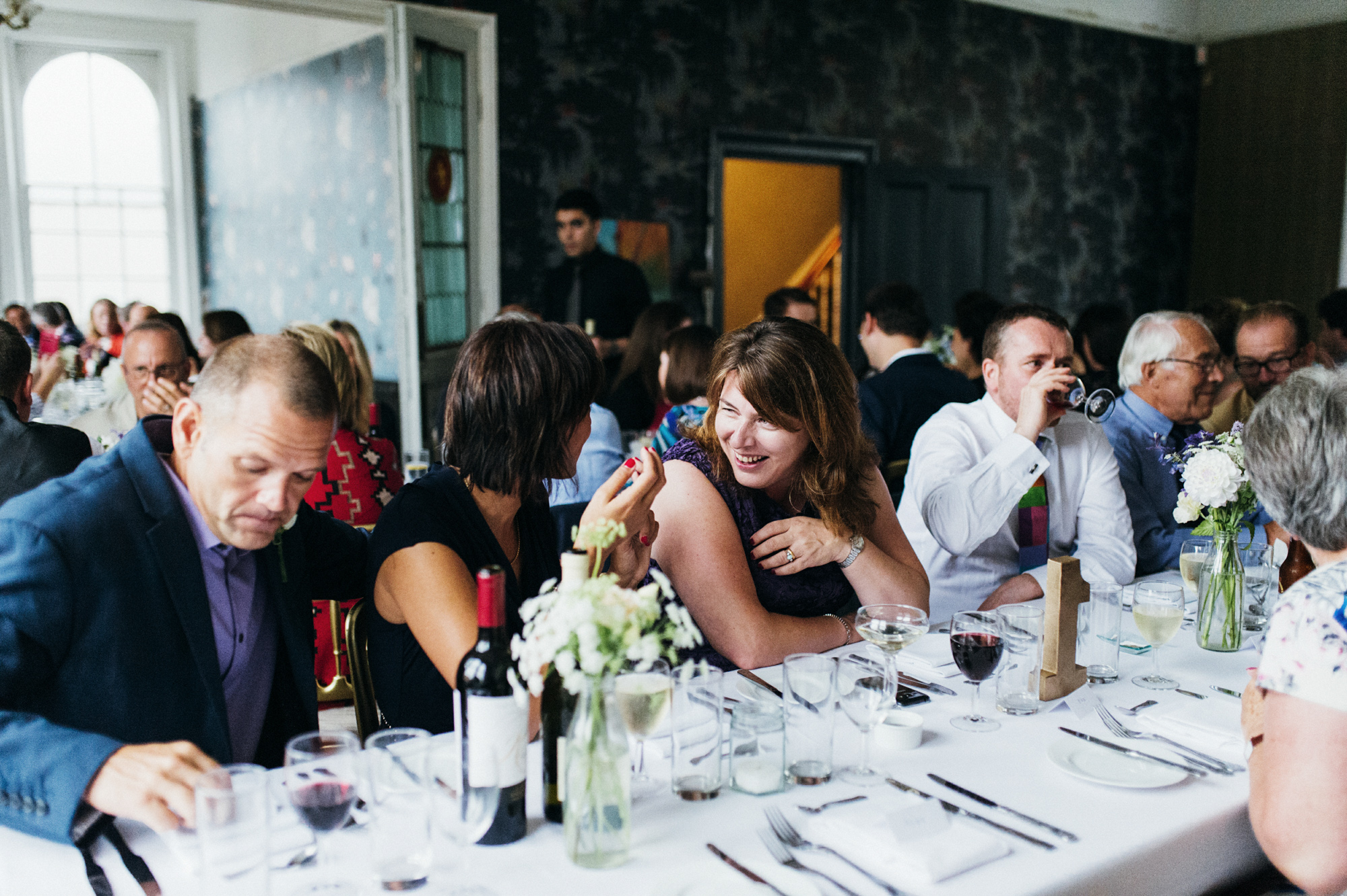 Laughing and drinking red wine - quirky creative gay friendly wedding photographer The Roost Dalston London wedding photographer © Babb Photo