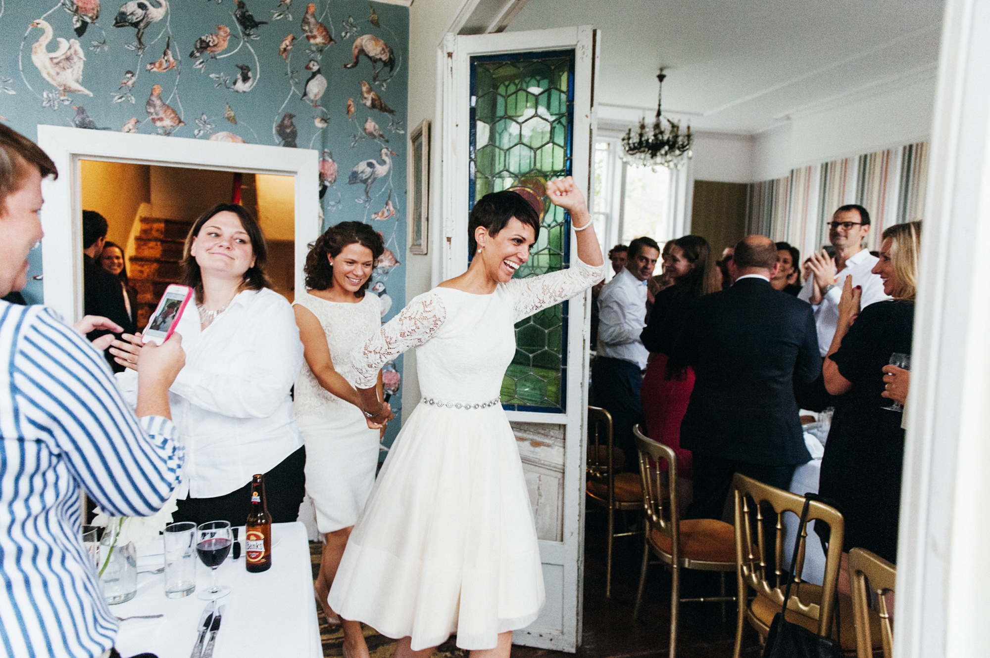 Lesbian brides enter, wedding guests cheer - quirky creative gay friendly wedding photographer The Roost Dalston London wedding photographer © Babb Photo