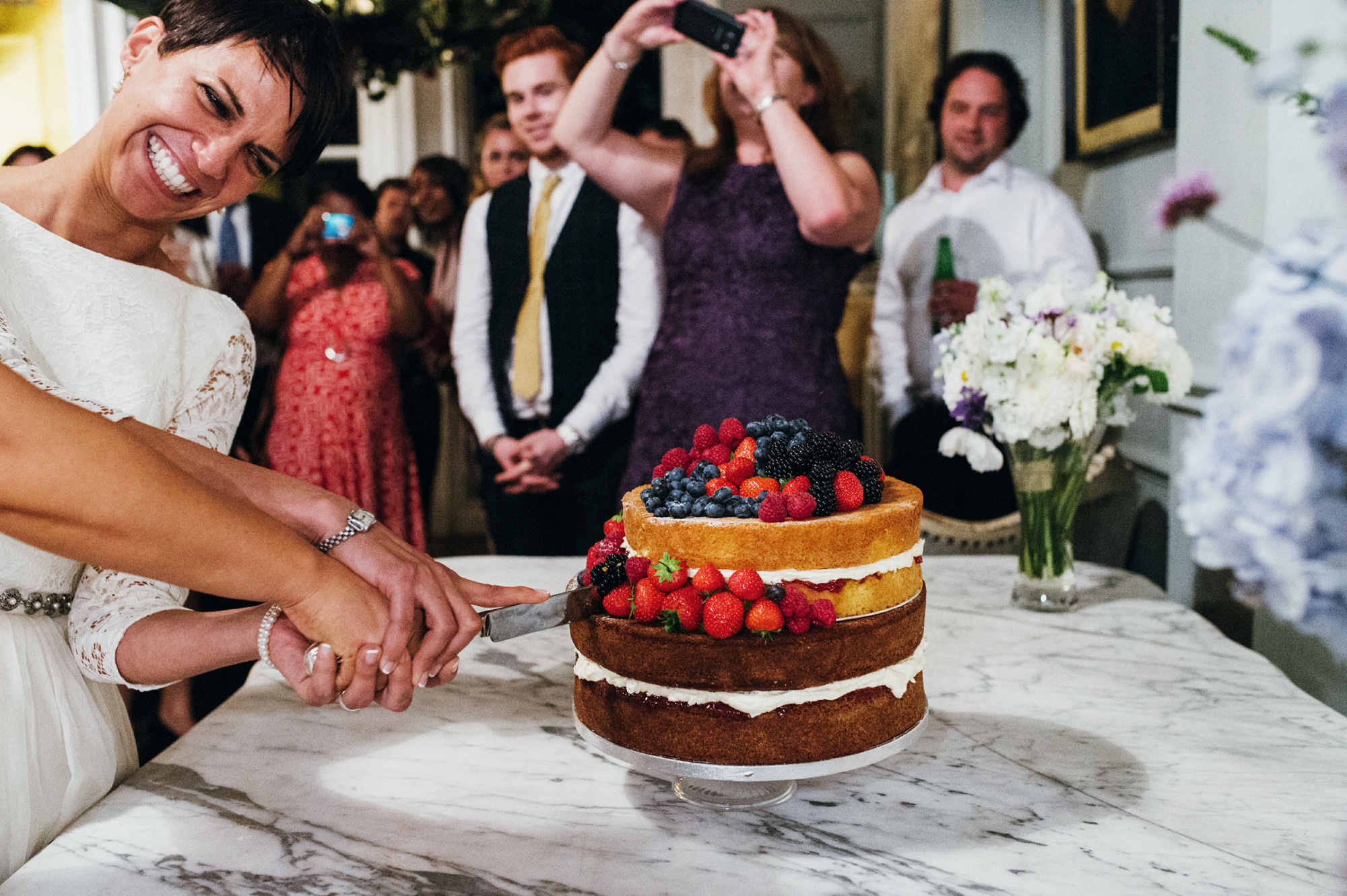 Cutting the naked wedding cake with strawberries - quirky creative gay friendly wedding photographer The Roost Dalston London wedding photographer © Babb Photo