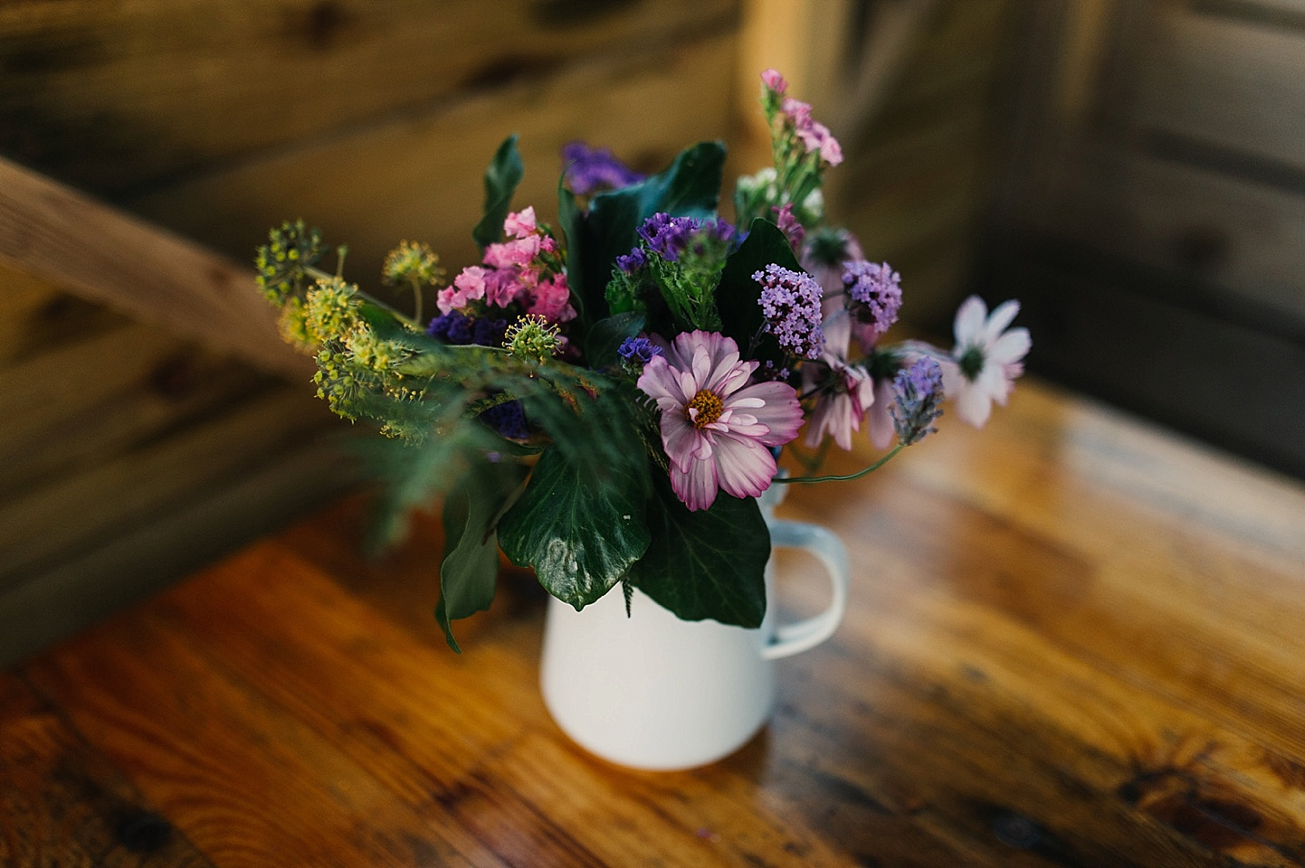 Wild flowers in a jug at rustic wedding venue in Wales - quirky Fforest wedding photography - Wales alternative wedding photography (c) Babb Photo - alternative wedding photographer