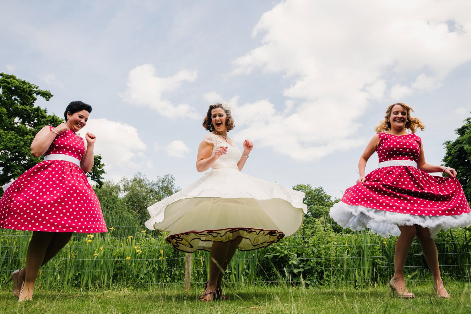bride and bridesmaids spinning in 50s dresses hampton court house wedding photography