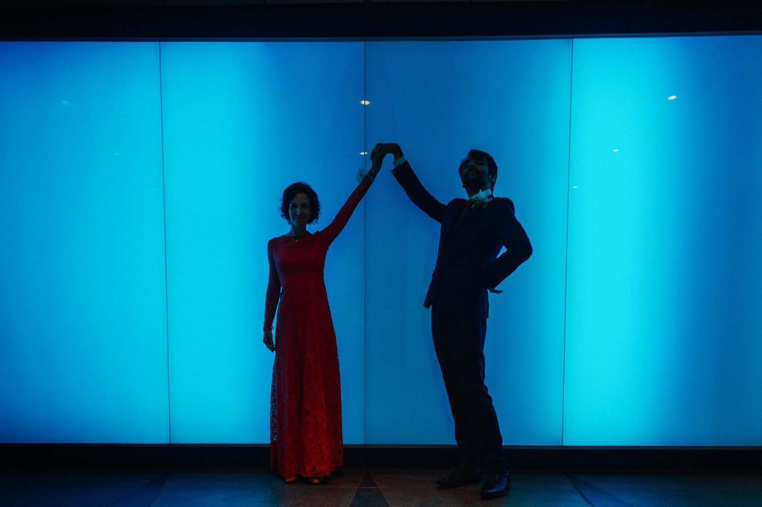 A wedding couple in shadow against a blue background in Kings Cross