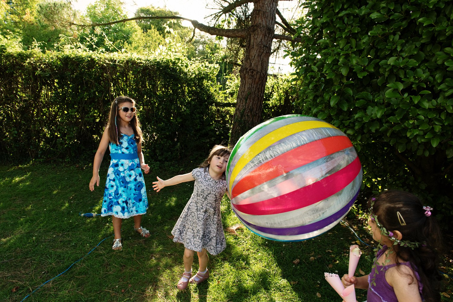 candid picture girl playing giant ball Old Luxters Barn Wedding Photography