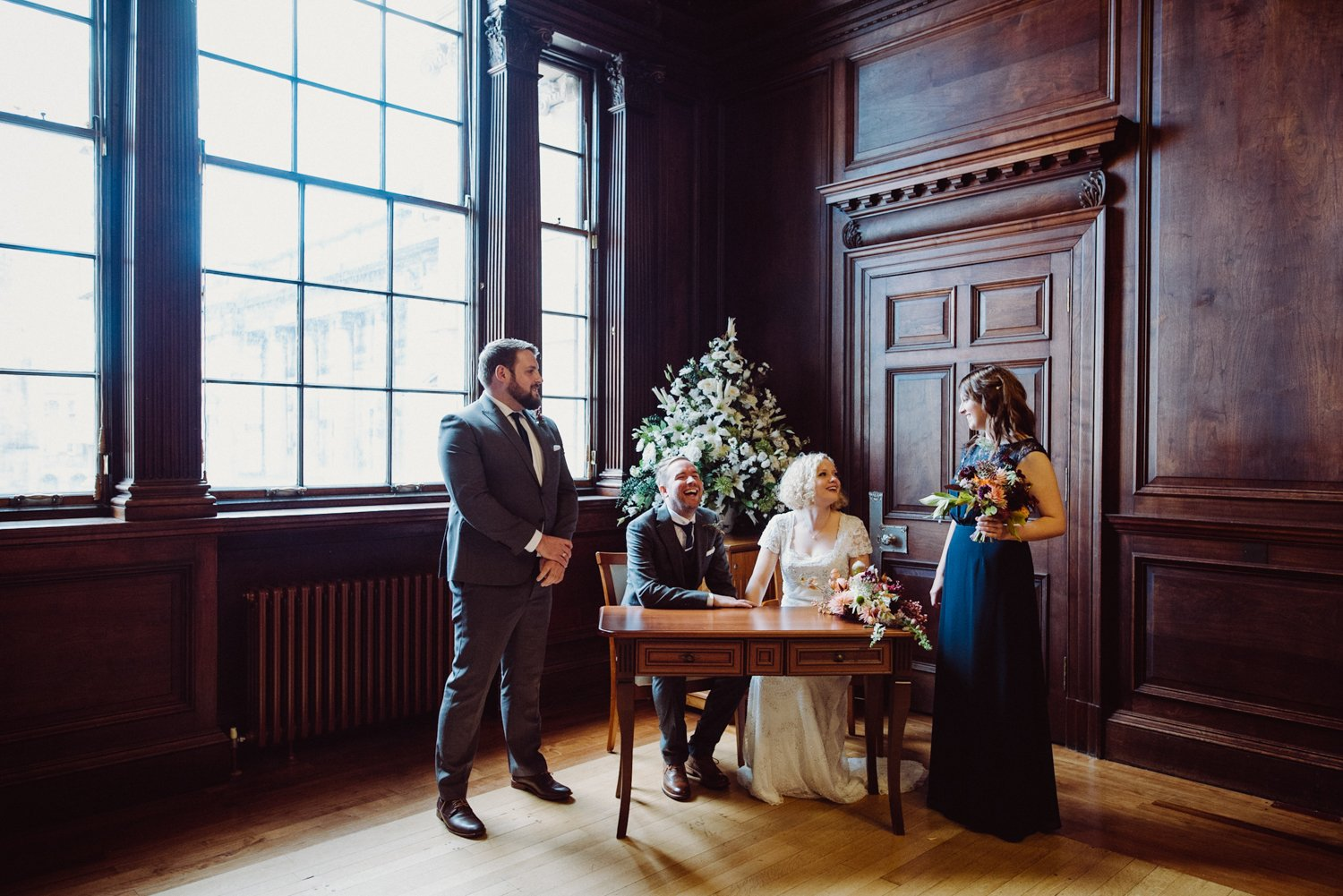 Phase Eight bride with Jigsaw groom signing register Scotland