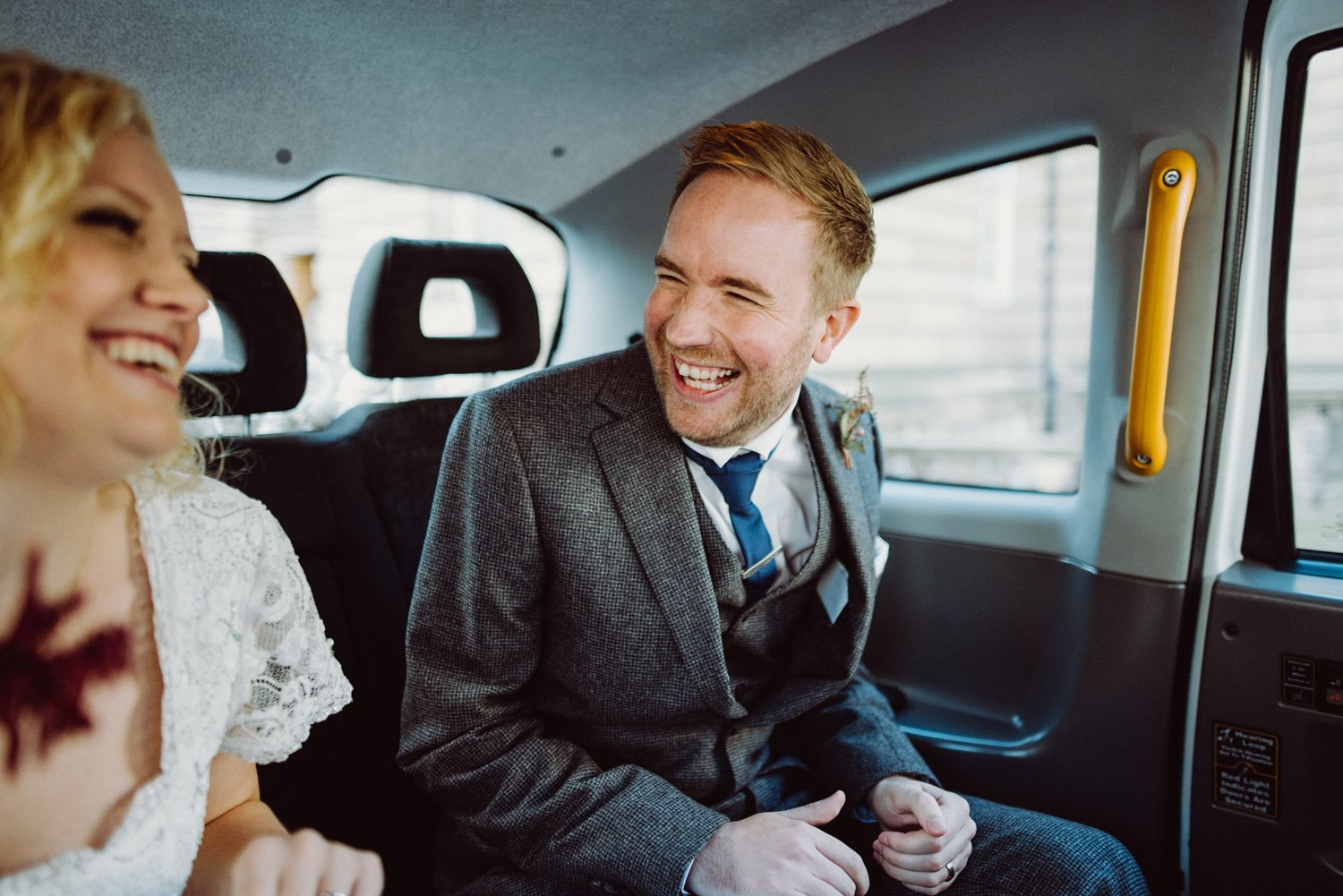 Jigsaw groom with bride giggling in Edinburgh taxi