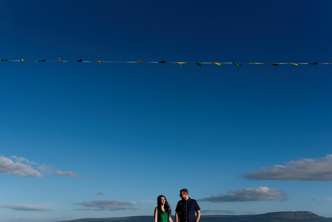 Couple in front of bunting Irish flag colours
