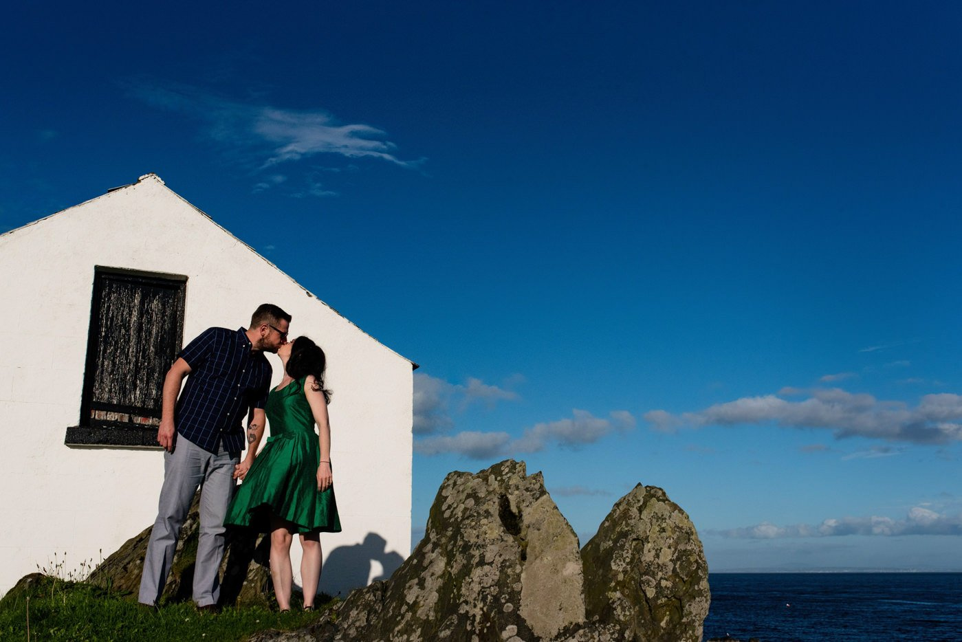 Couple kissing in front of whitewashed house greencastle-donegal-pre-wedding_