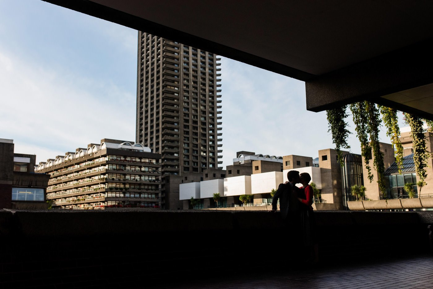Couple in shadow against backdrop of Barbican centre in London