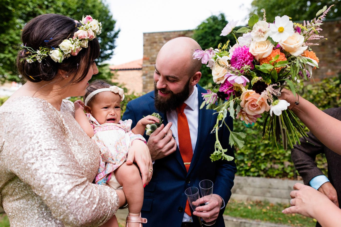 Couple hold crying baby Tab Venue Shoreditch Wedding Photography