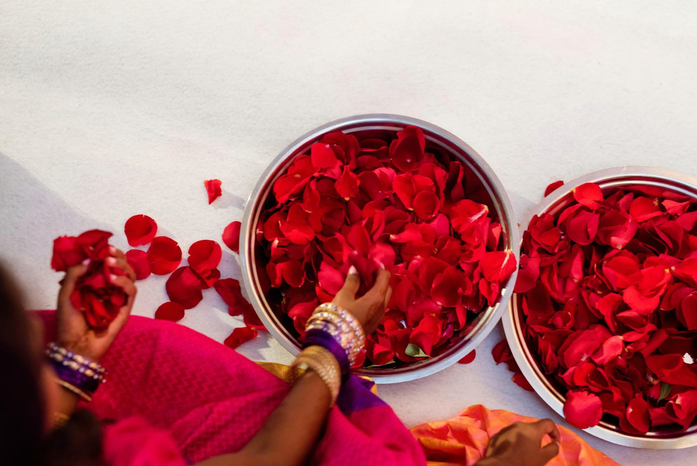 Vibrant red petals at Hindu wedding Painshill Park Conservatory Surrey