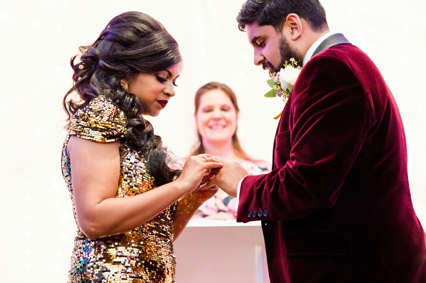 Bride wearing gold dress with groom wearing red velvet jacket exchange rings Surrey wedding