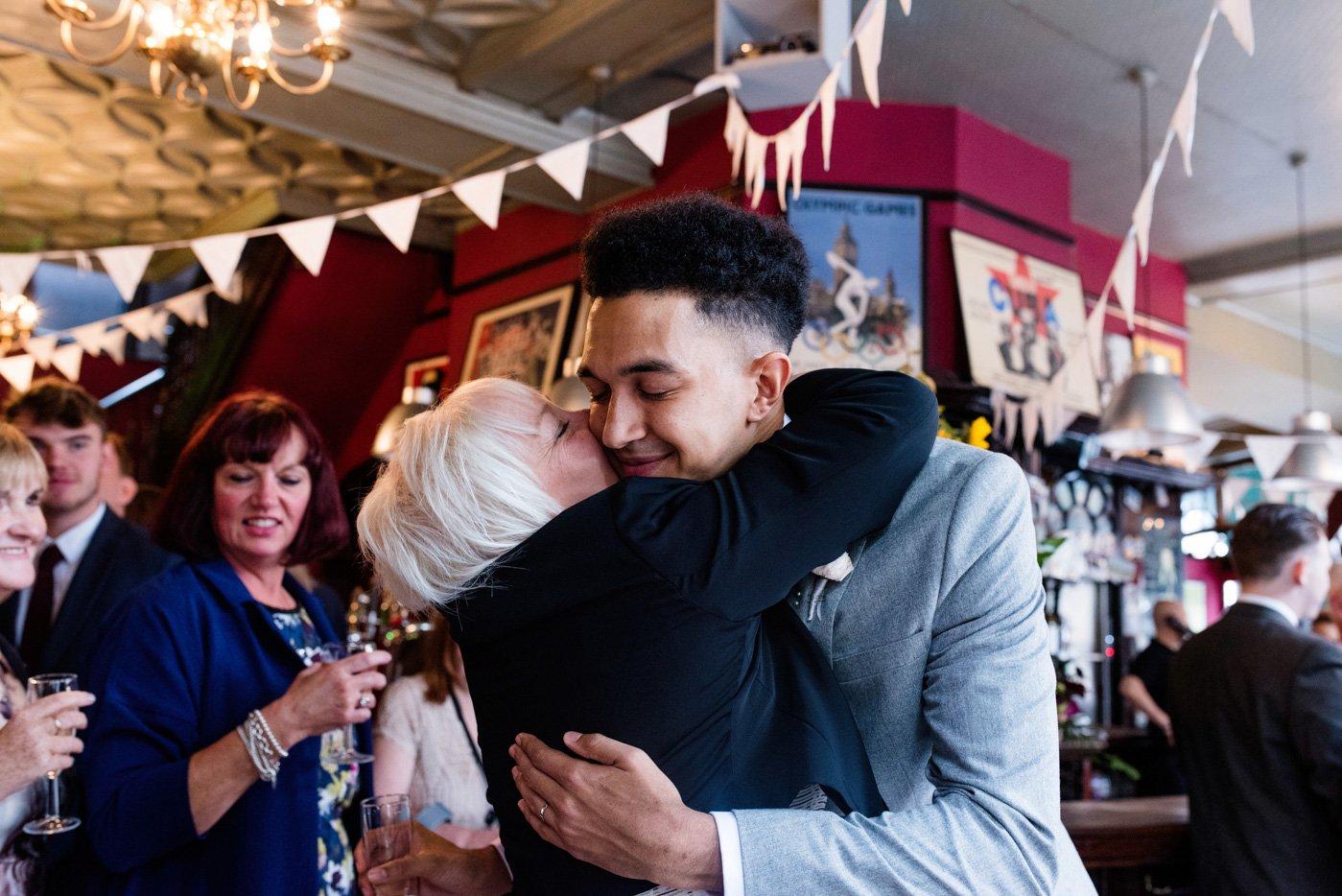 Cuddles with groom at London pub wedding