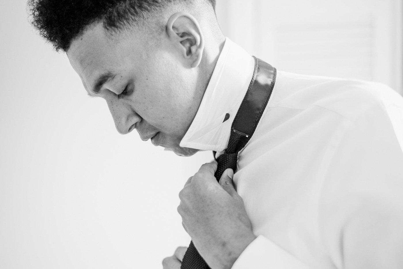 Alternative groom putting on tie pre wedding London