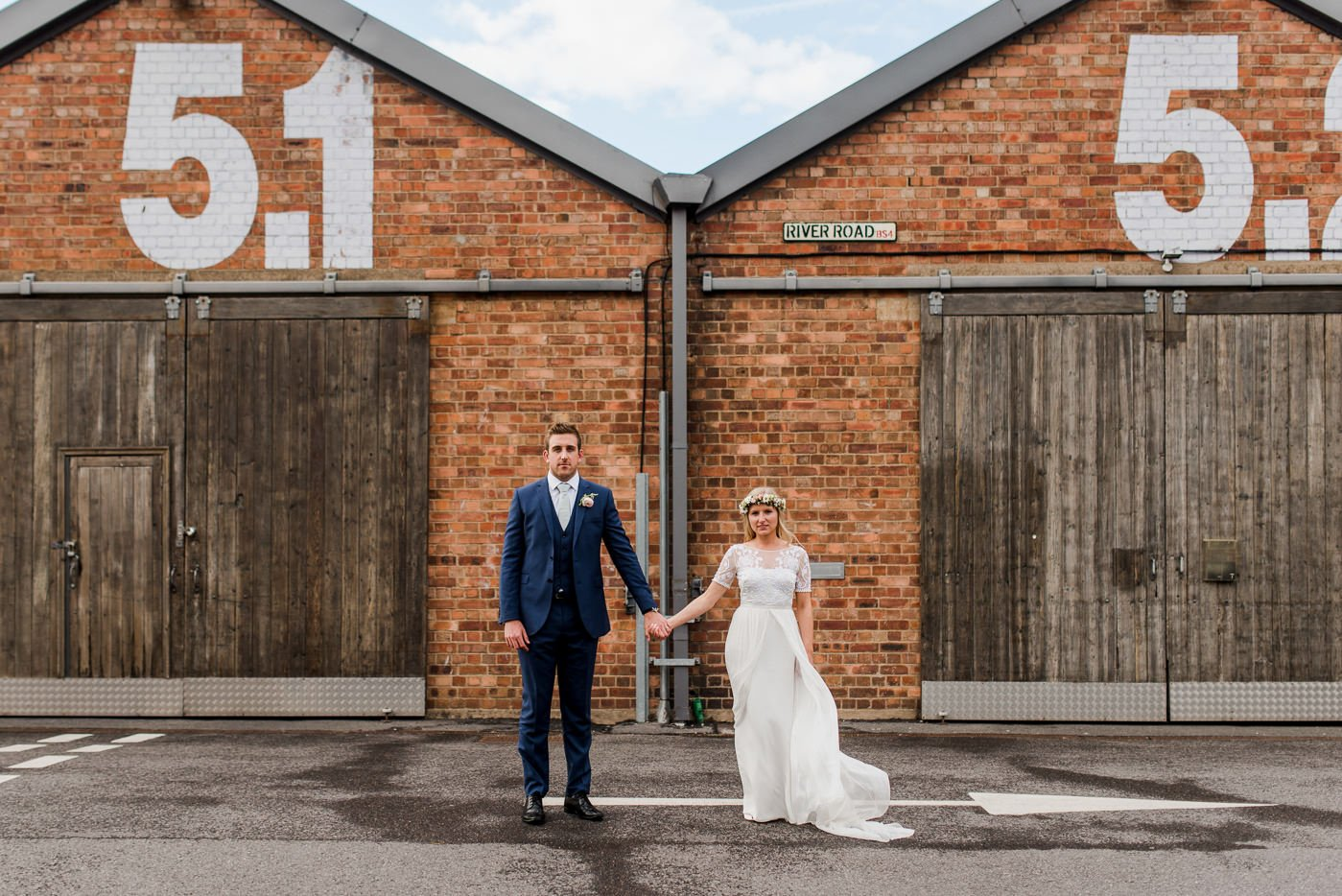Quirky example of warehouse wedding photography with a bride and groom standing outside of the warehouses at The Paintworks, Bristol on their wedding day