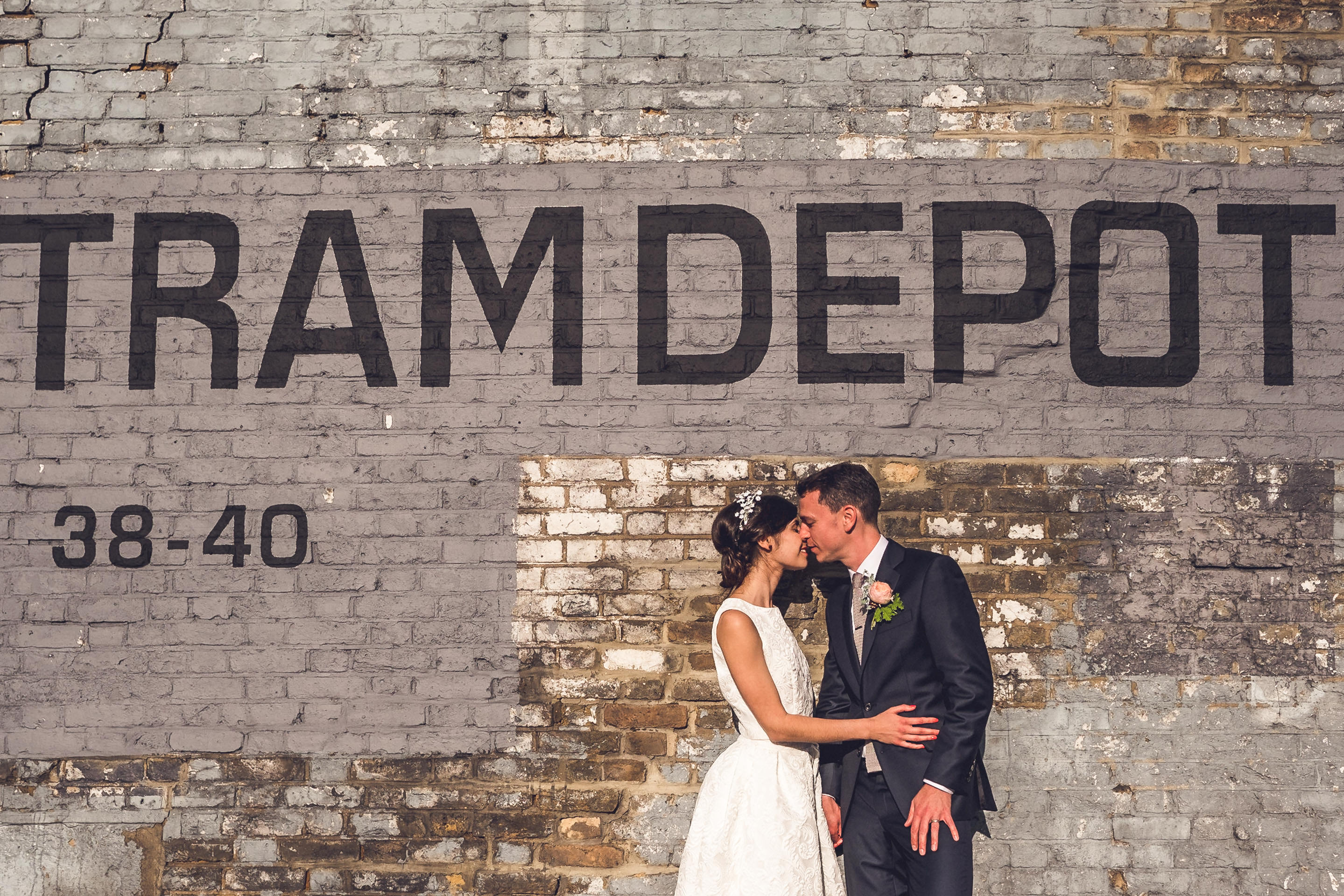 Urban portrait of hip bride and groom in front of clapton tram depot