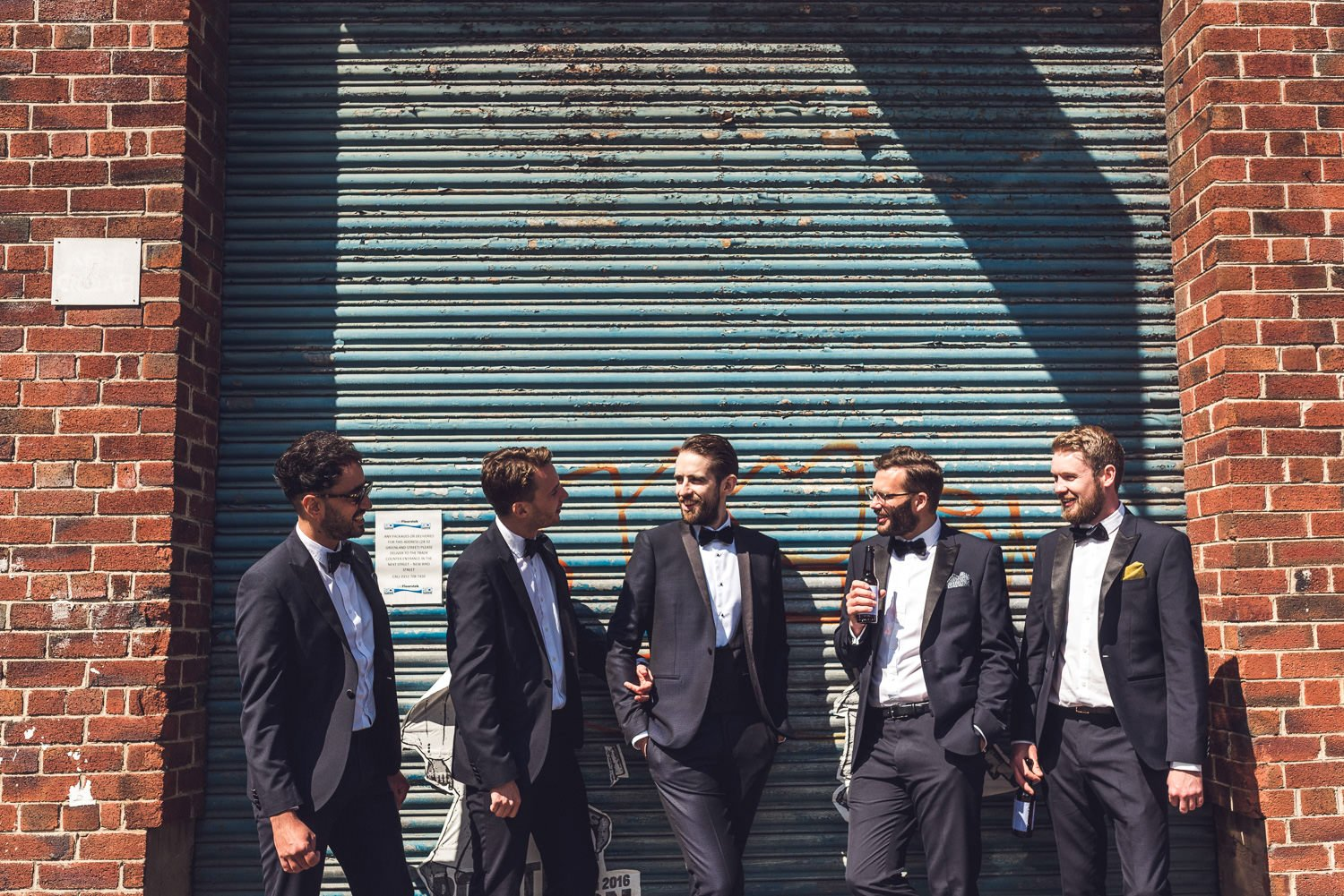 Ushers in tuxedos in front of rusted metal shutters Constellations Liverpool wedding photography