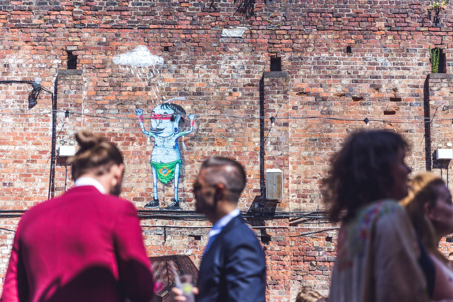 Wedding guests drink in sunshine in front of graffiti wall Constellations Liverpool wedding photography