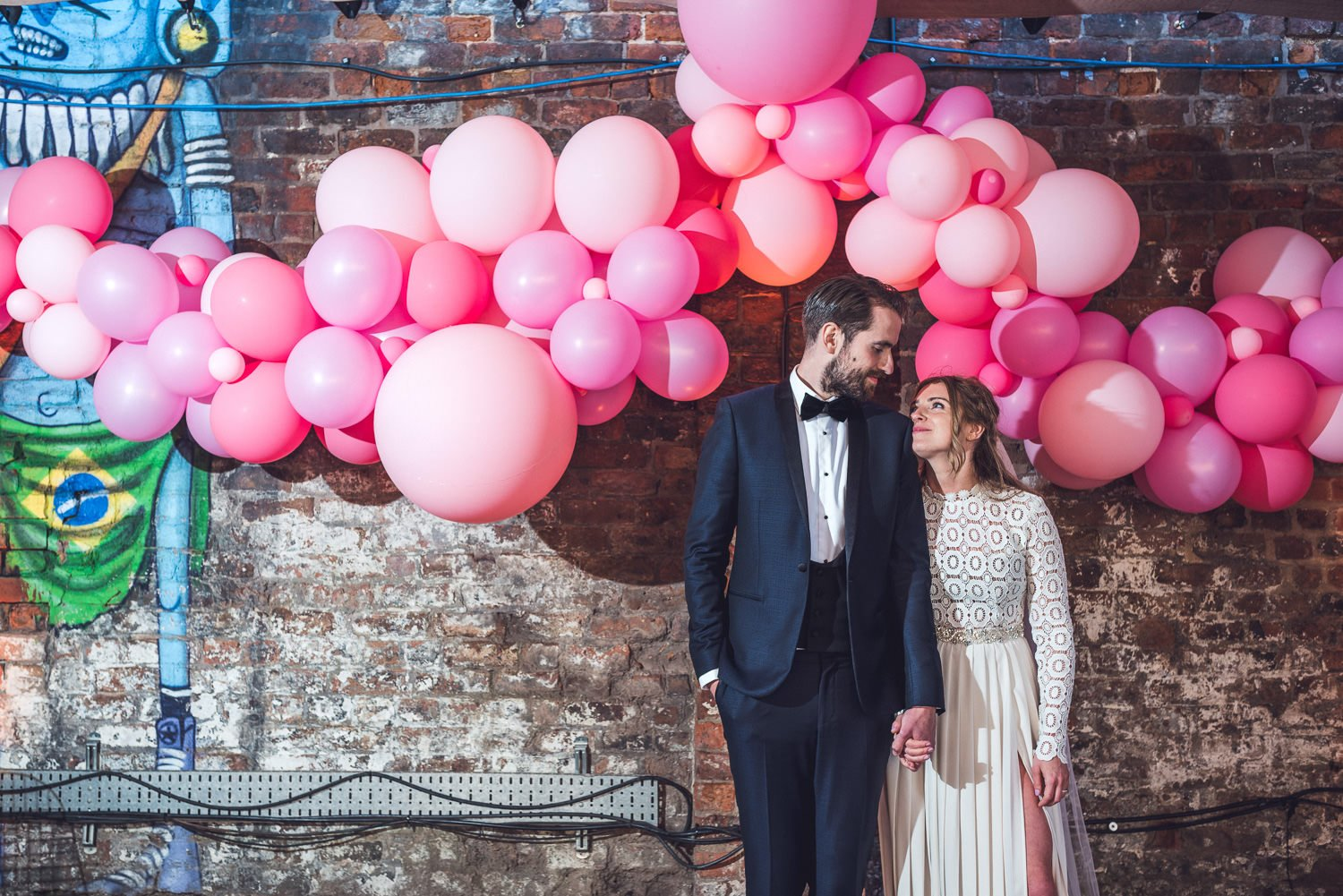 Bride and groom with pink balloon installation Constellations Liverpool wedding photography