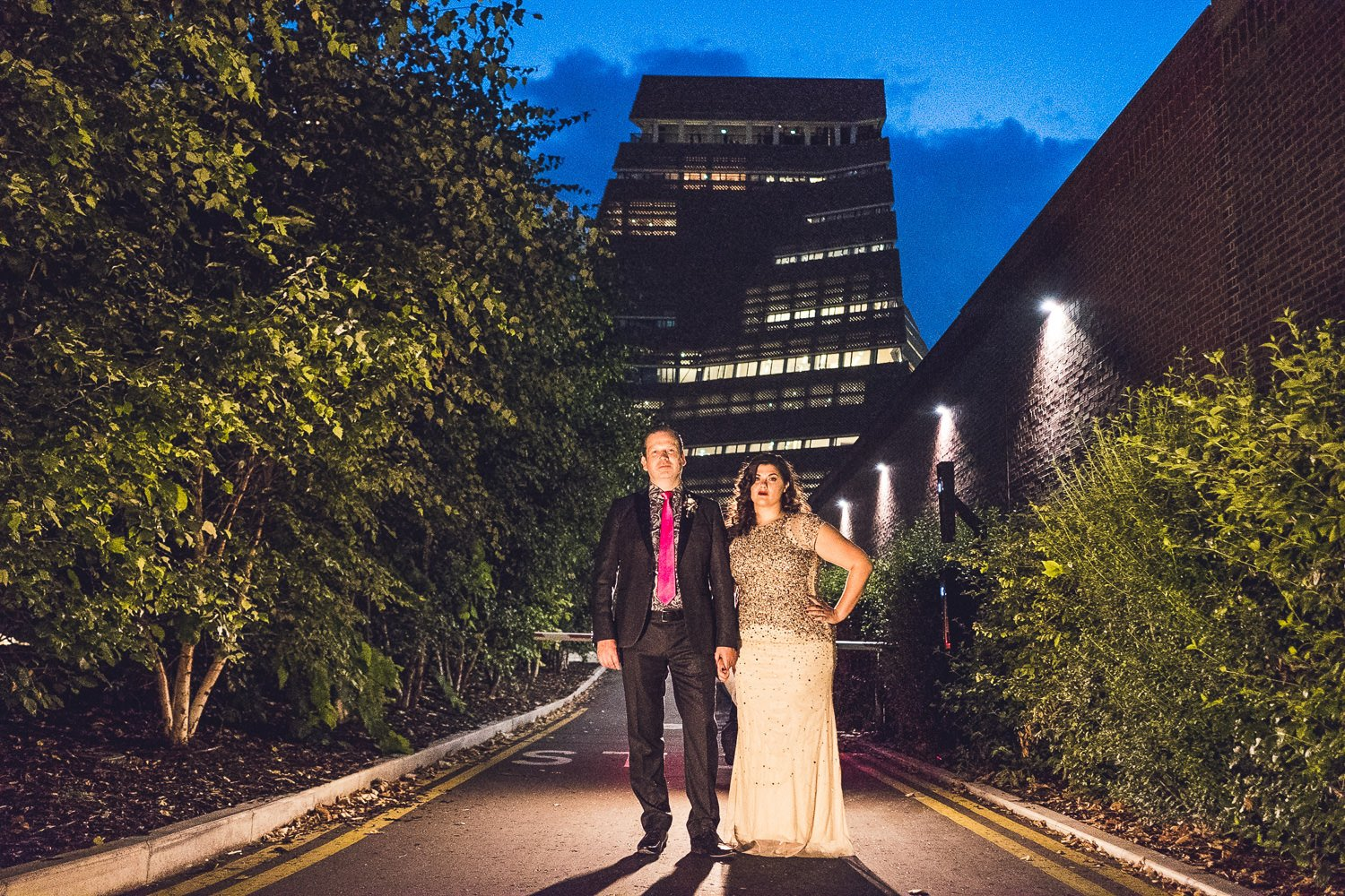 Night time portrait of couple in front of tate modern bride in gold sequins