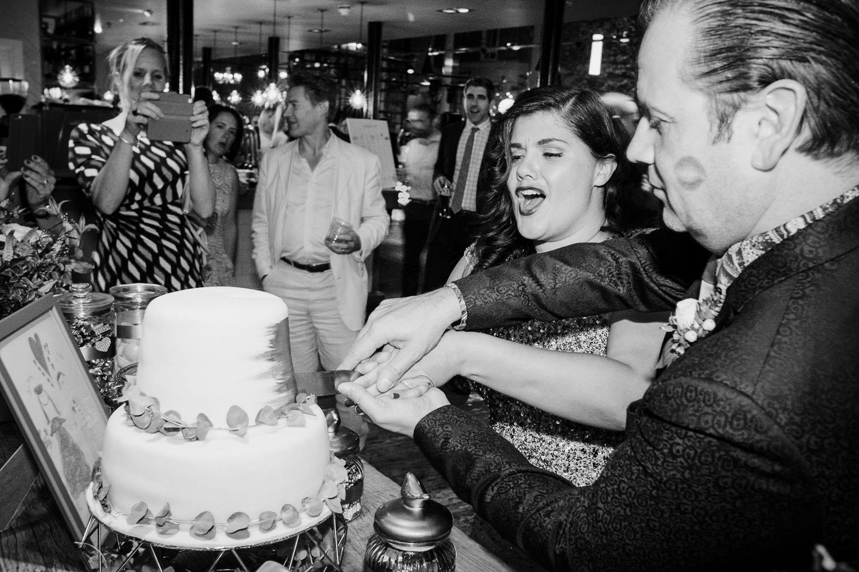 Black and white image of couple cutting wedding cake