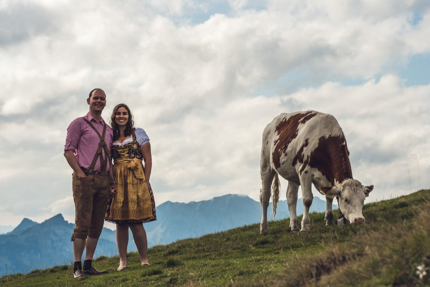 Couple in traditional Swiss dress standing next to cow