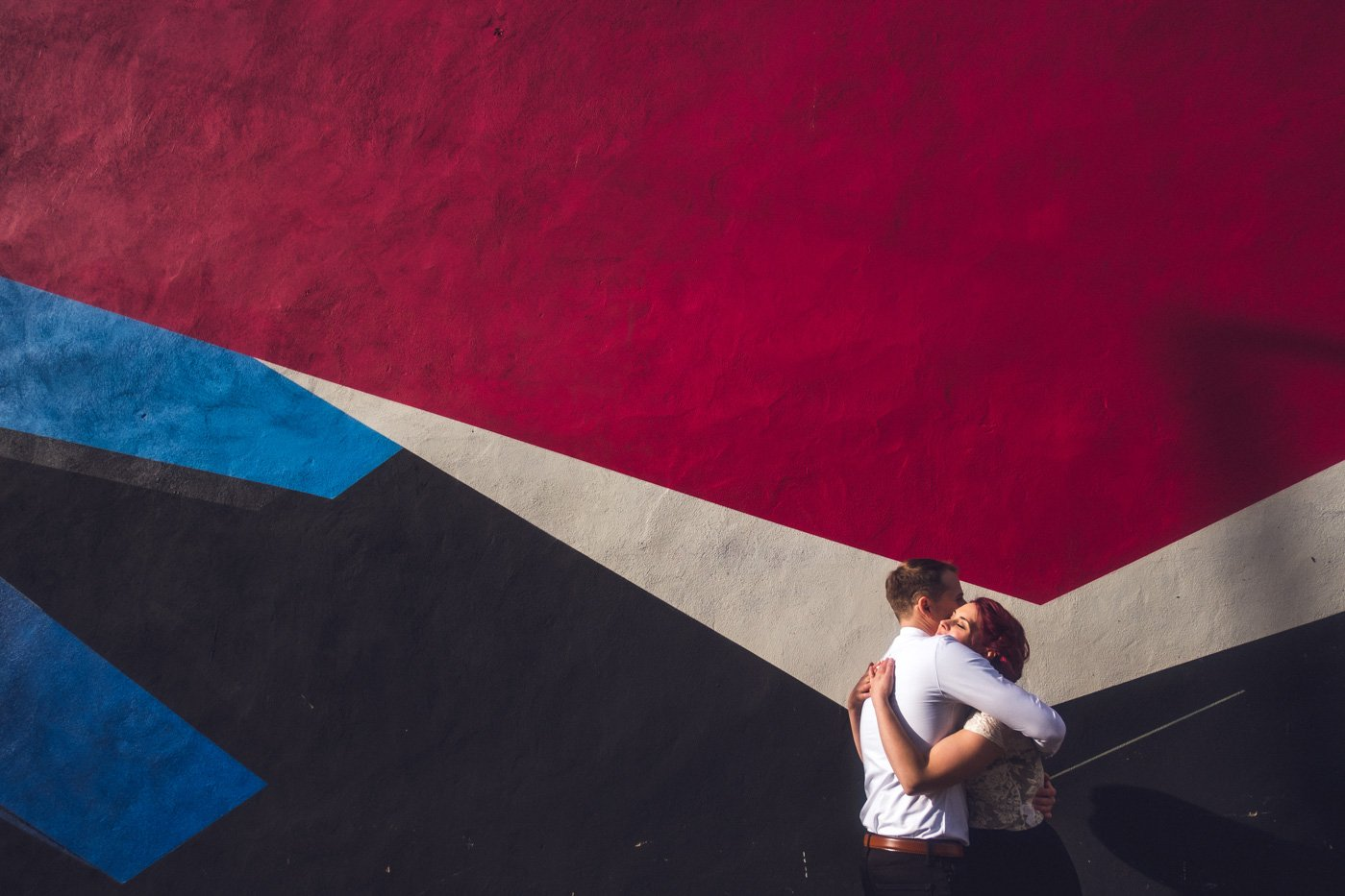 Couple hugging in front of Walthamstow graffiti wall