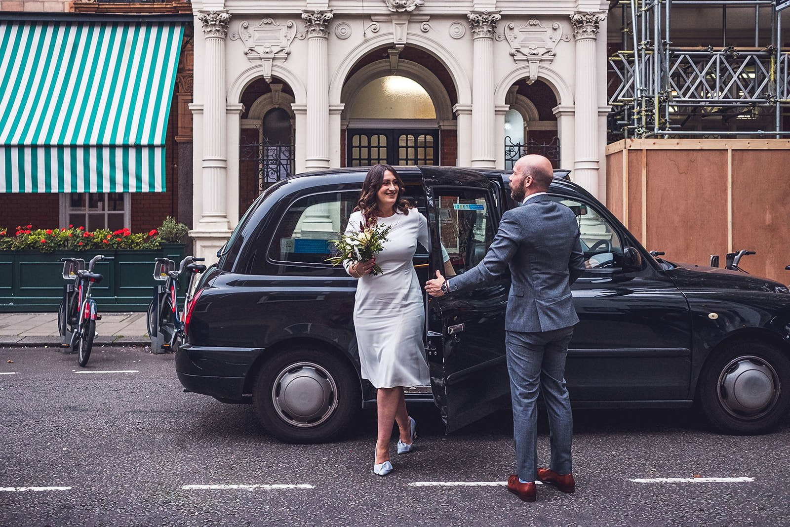 Couple getting out of black taxi London elopement photographer