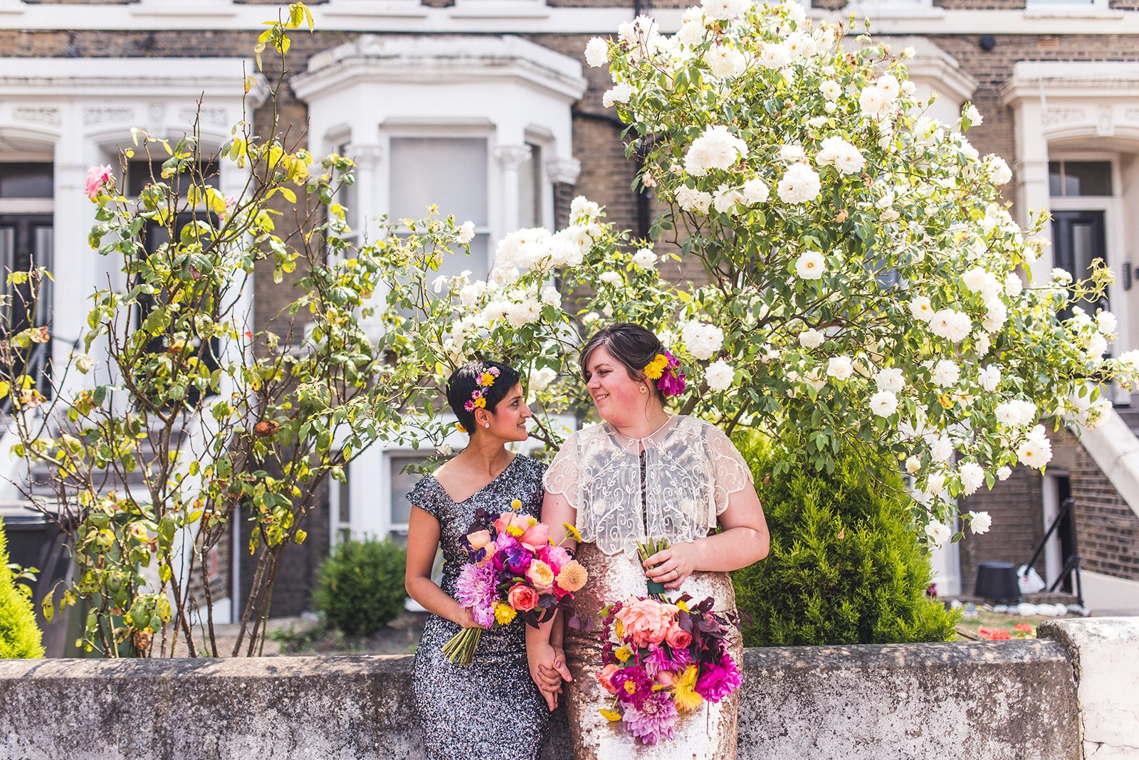 Two brides dressed in sequins holding colourful flowers sitting on a wall after their Myatts Field bandstand wedding