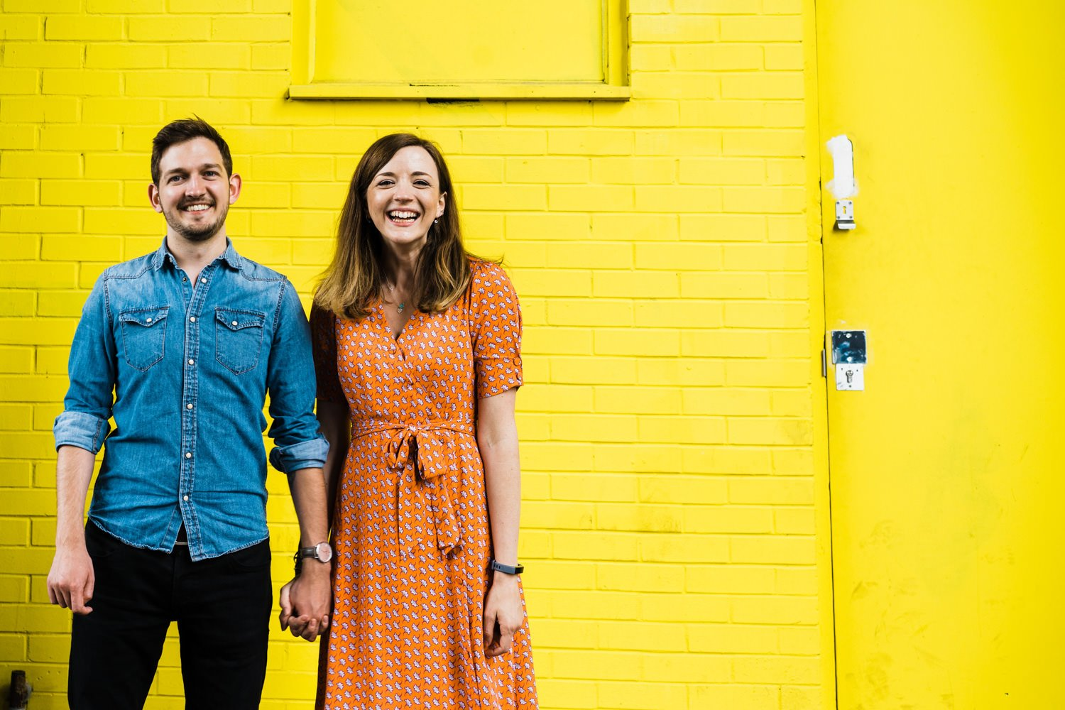 Couple against a yellow backdrop in Digbeth Birmingham