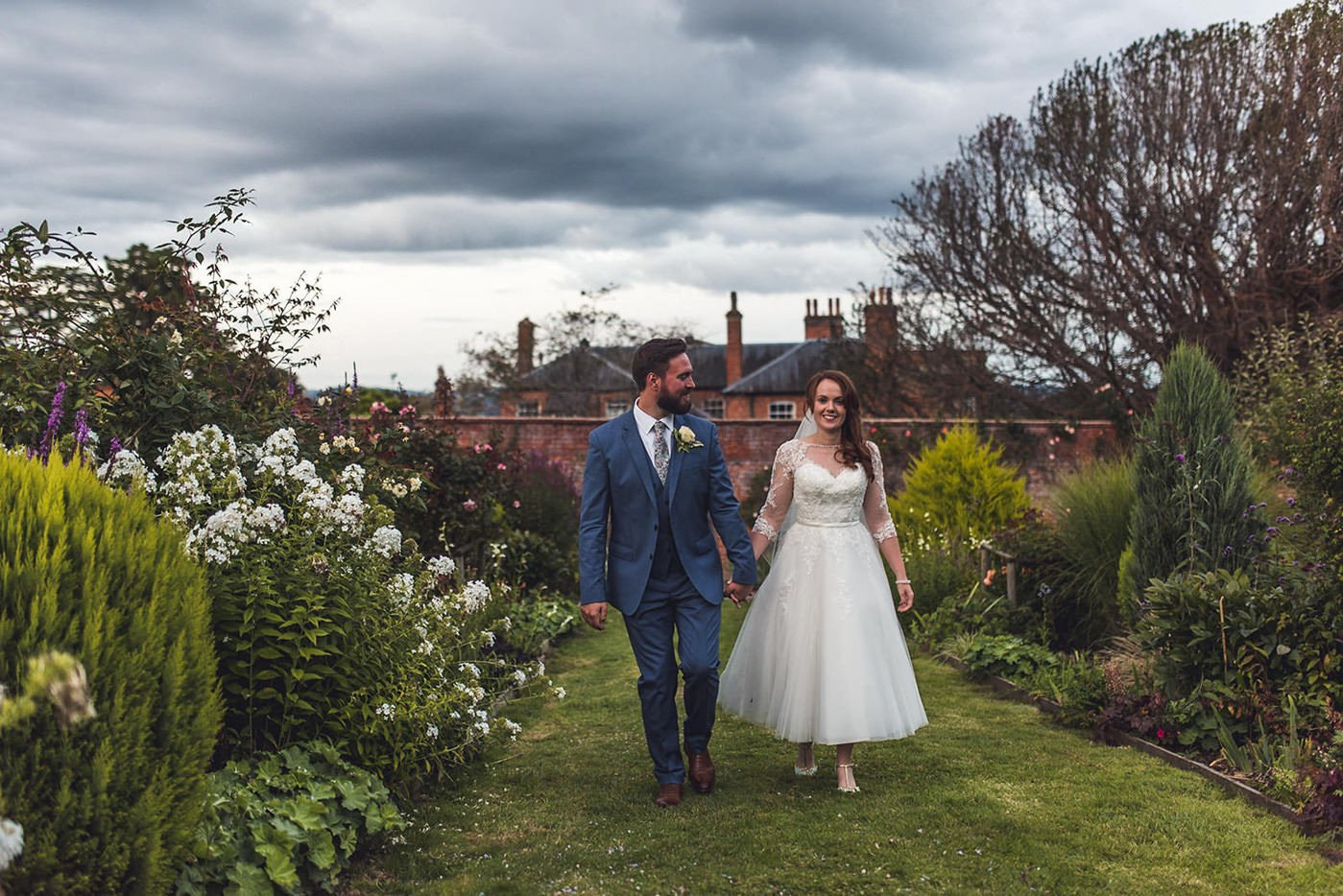 A bride and groom walk through walled garden at Homme House