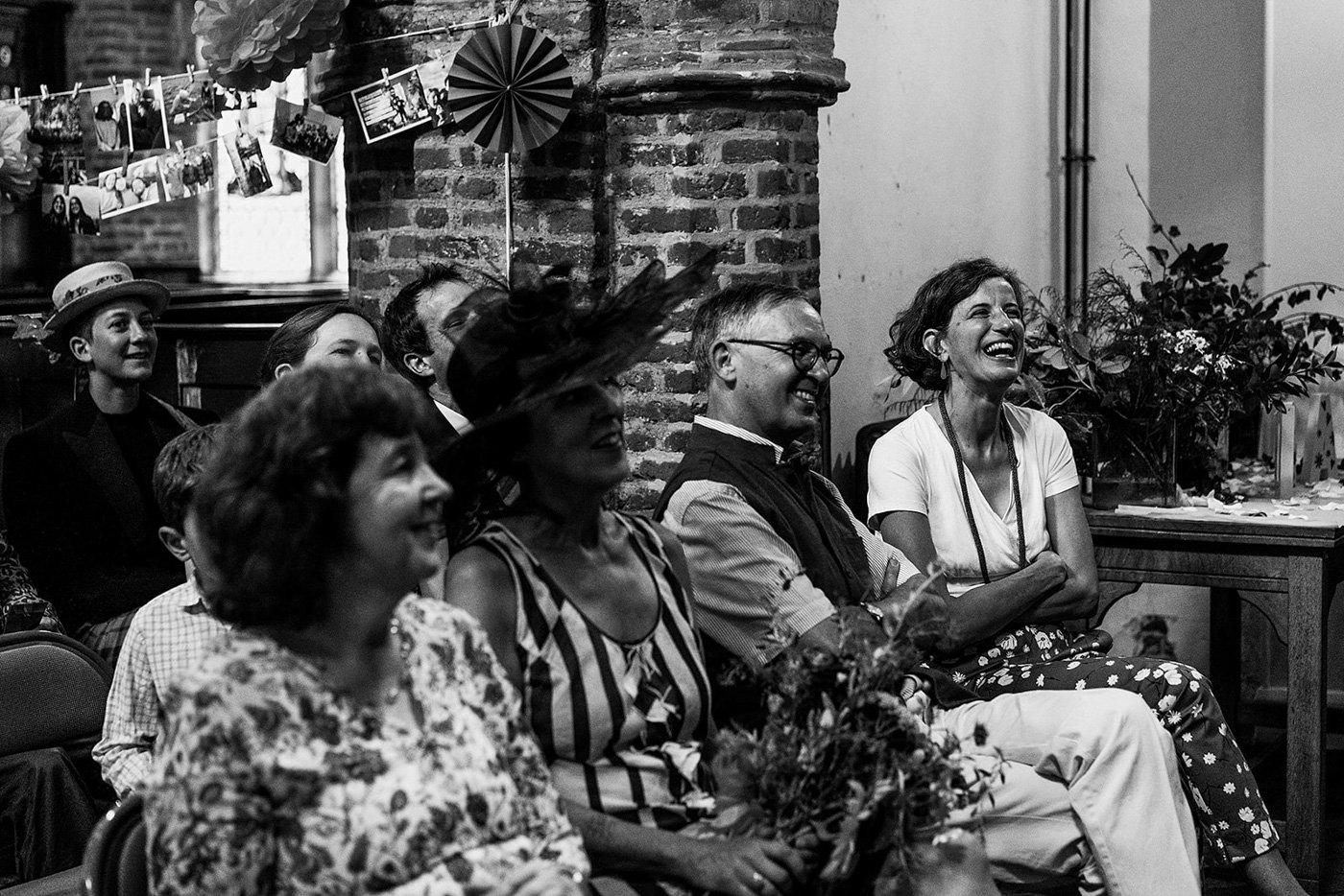 Black and white shot of guests laughing at humanist wedding ceremony