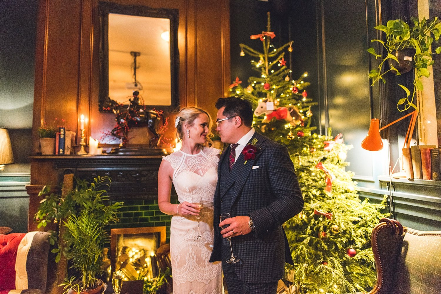 Bride and groom in front of Christmas tree at London pub