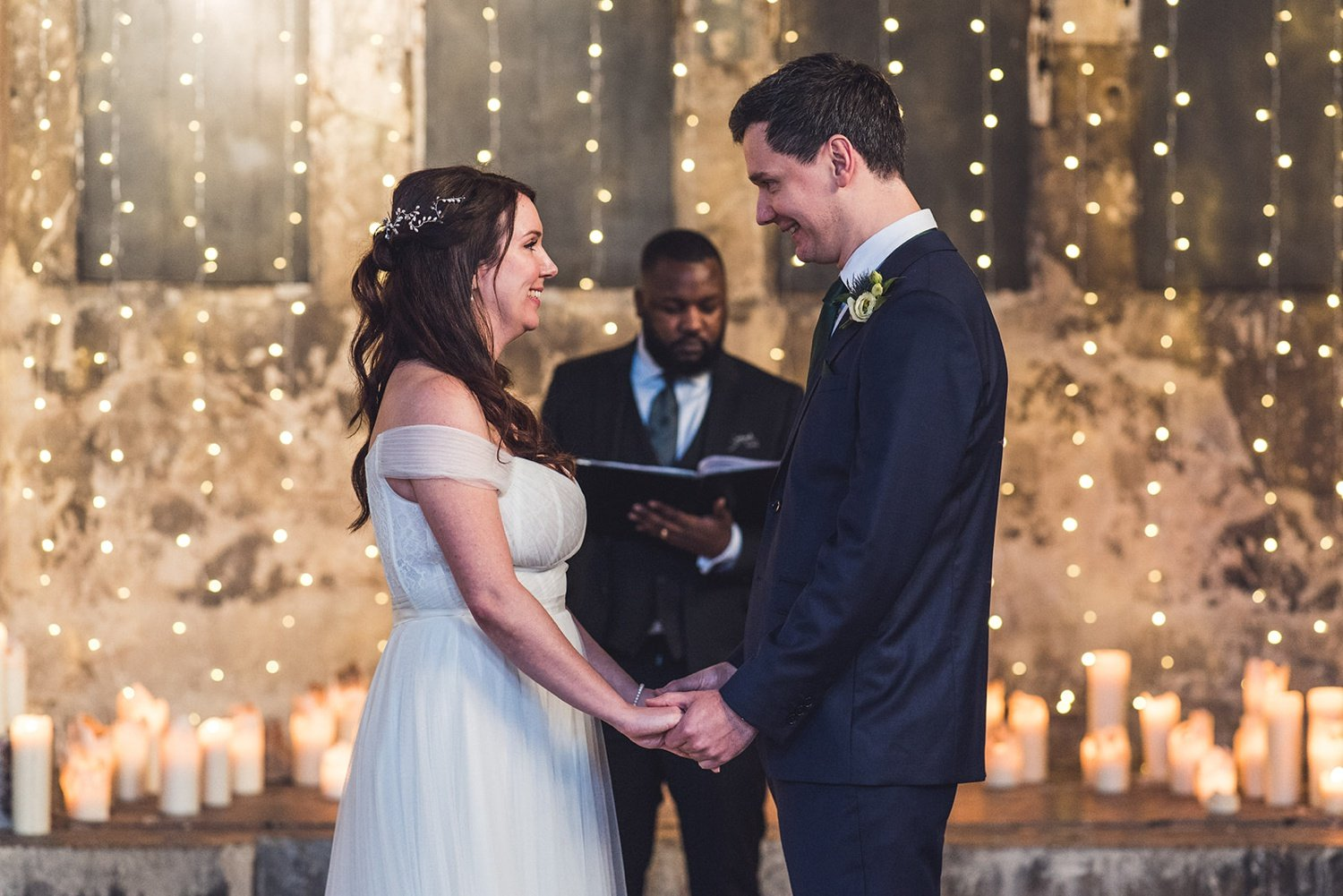 Bride and groom getting married in front of fairy lights at The Asylum Chapel