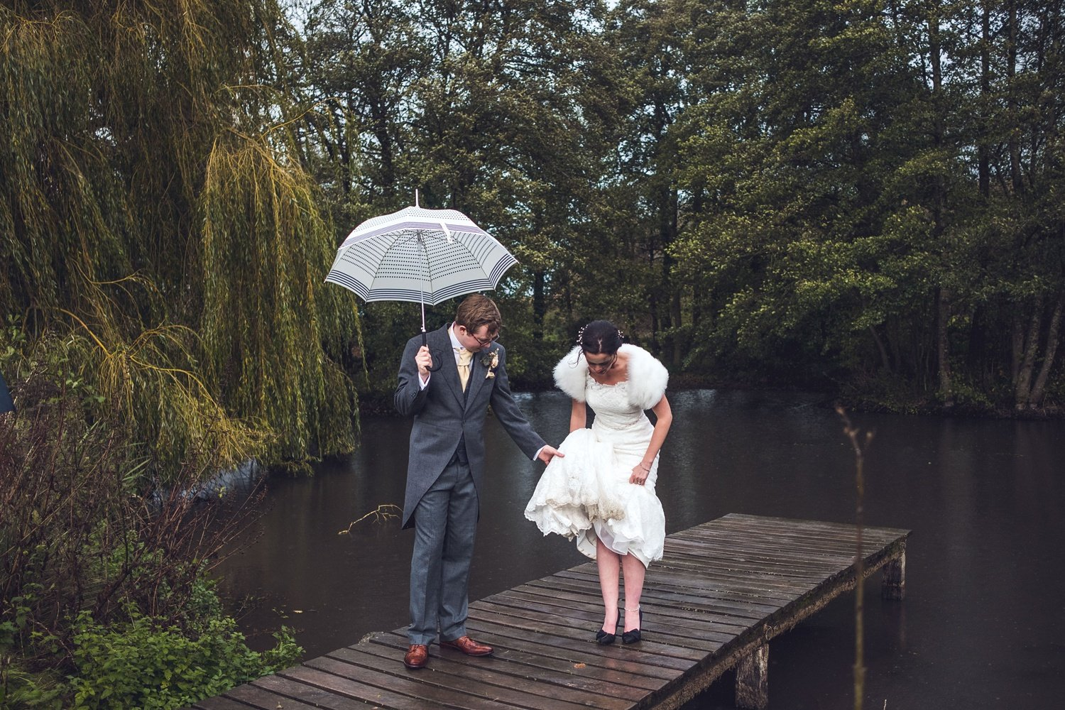 Bride and groom on jetty in rain at Dewsal Court