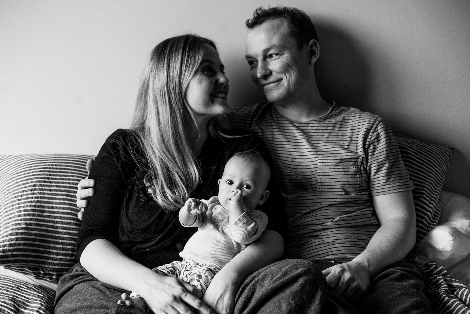 Black and white image mum dad and baby looking happy South London Family Photography